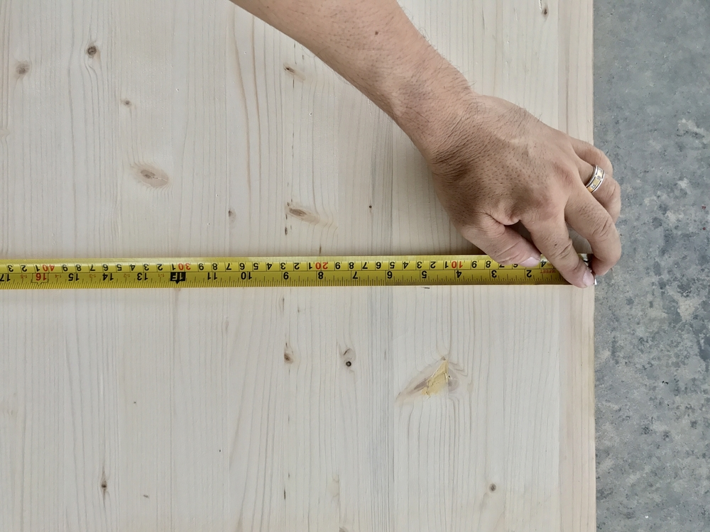 Man measuring table top with measuring tape