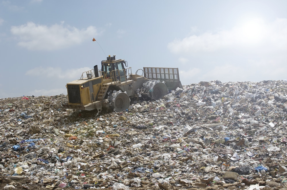 Bulldozer compressing rubbish at rubbish dump
